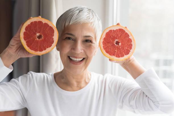 Mature woman holding grapefruit stock photo