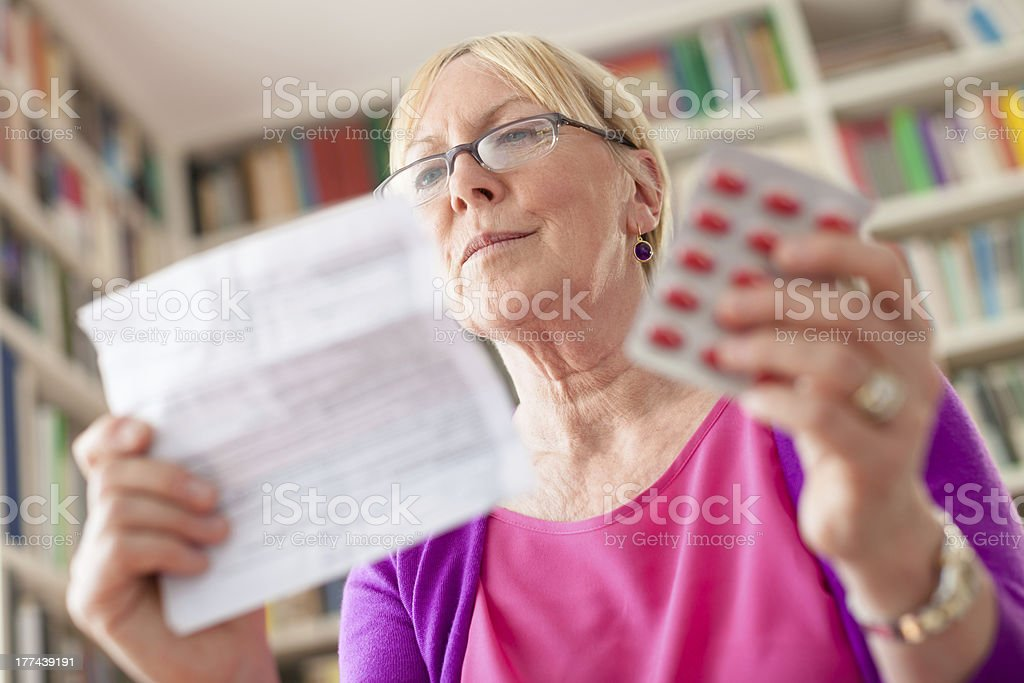 Mature woman holding pills and drug prescription stock photo