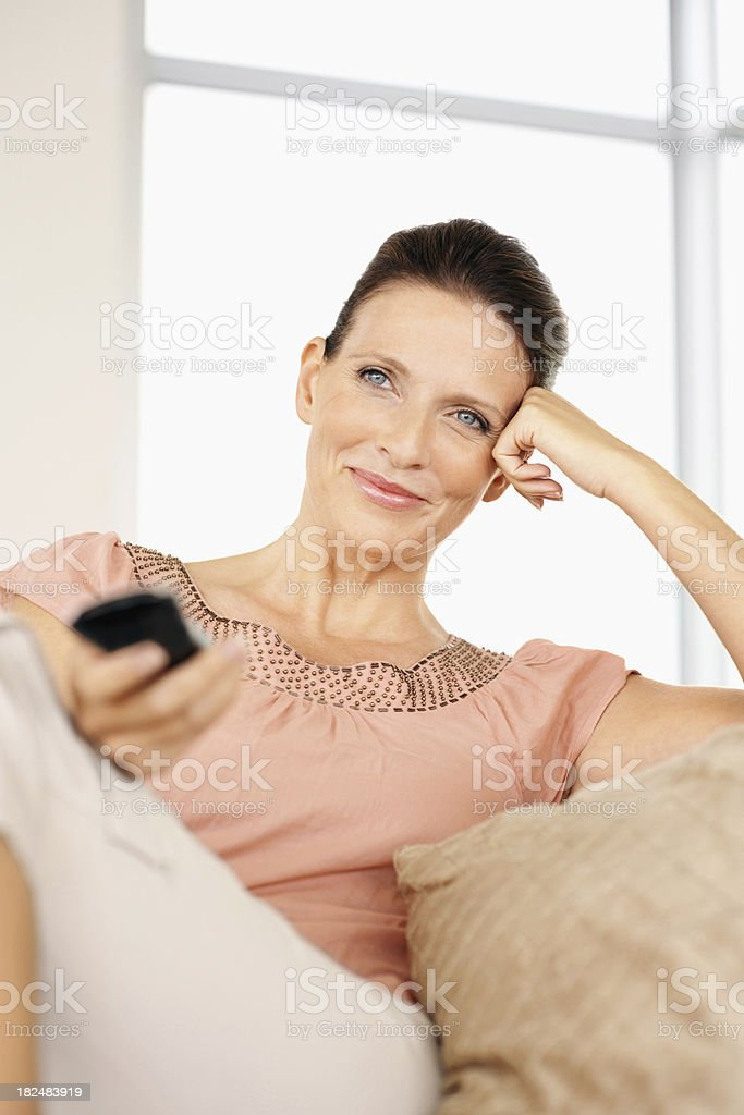 Mature woman holding remote control stock photo