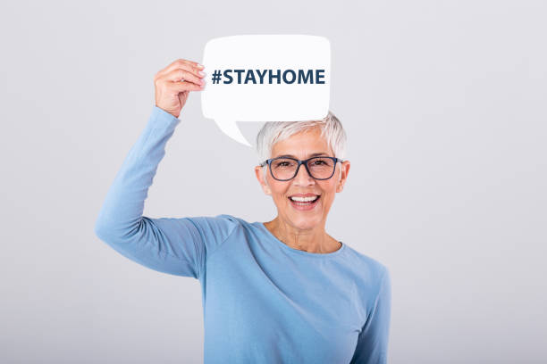 Mature woman holding Stay home phrase #stayhome on speech bubble isolated on background. Mature woman holding Stay home phrase #stayhome on speech bubble isolated on background. stay at home order stock pictures, royalty-free photos & images