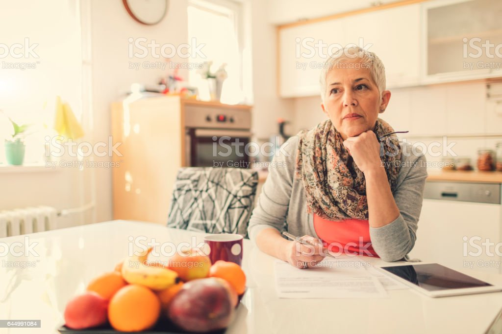 Mature woman Home budgeting in her dining room by the table with...