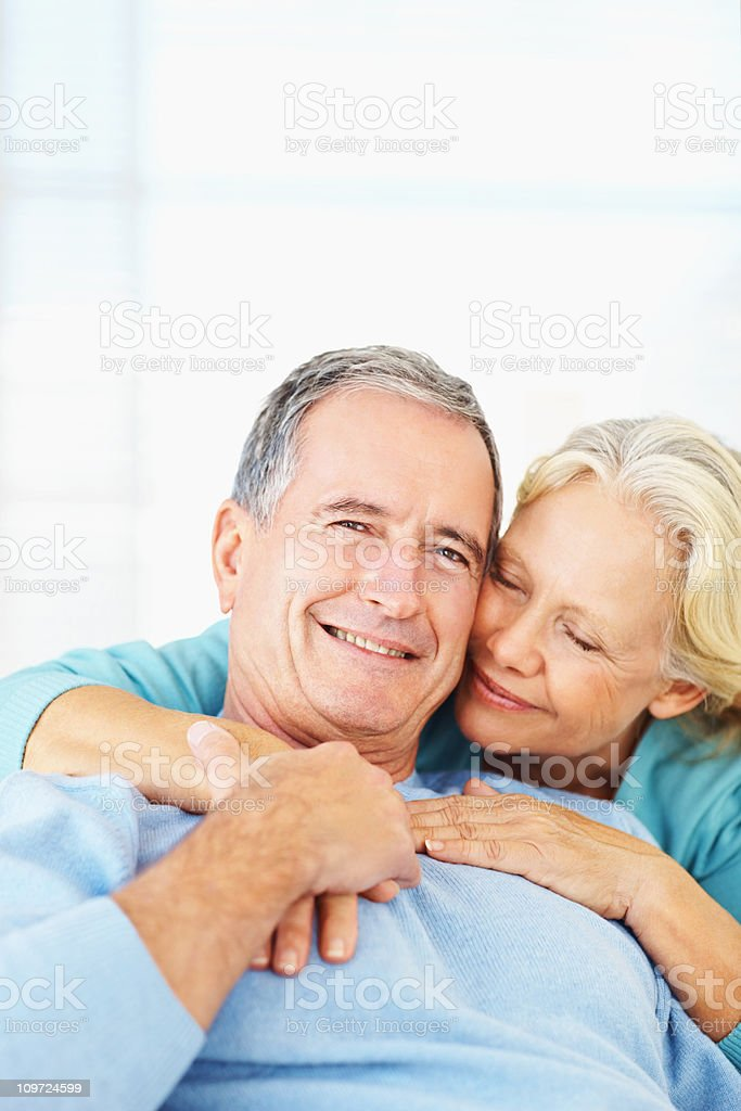 Mature woman hugging her husband from behind royalty-free stock photo