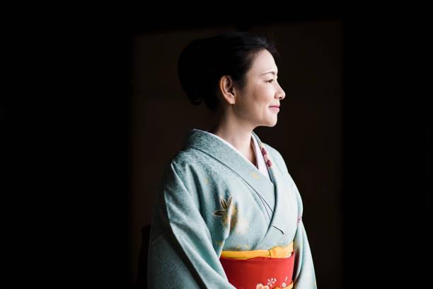 reife frau in einem kimono in einem tempel - kimono stock-fotos und bilder