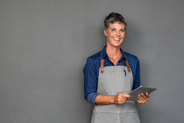 Mature woman in apron holding digital tablet Successful mature woman in apron standing and holding digital tablet against grey wall. Happy small business owner holding tablet and looking at camera. Smiling portrait of entrepreneur standing satisfied with copy space. apron stock pictures, royalty-free photos & images