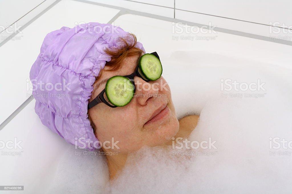 Donna matura in una vasca da bagno con fettine di cetriolo per