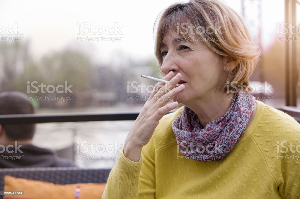 Mature woman in cafe outdoors stock photo