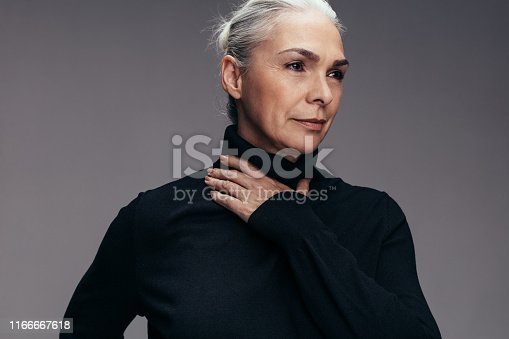 Senior woman in black t-shirt standing on grey background. Mature woman in casuals looking away.