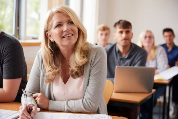 mature woman in college attending adult education class - adult student stock photos and pictures