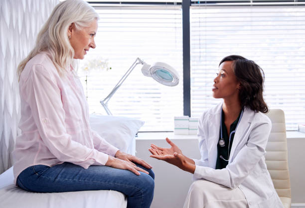 成熟的女人在諮詢與女醫生坐在檢查沙發在辦公室 - 女性 個照片及圖片檔