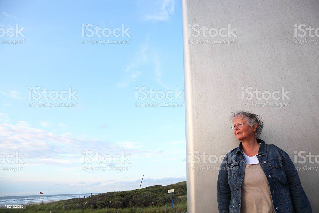 mature woman in denim jacket looks at seascape stock photo