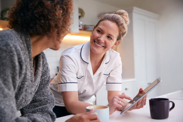 Mature Woman In Dressing Gown At Home Talking With Female Nurse With Digital Tablet stock photo