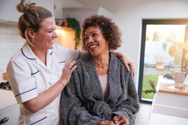Mature Woman In Dressing Gown Talking With Female Nurse In Kitchen At Home stock photo