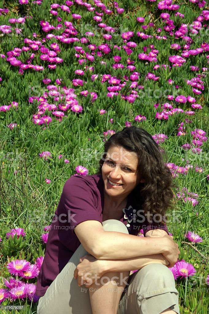Mature woman in front of flowers royalty-free stock photo
