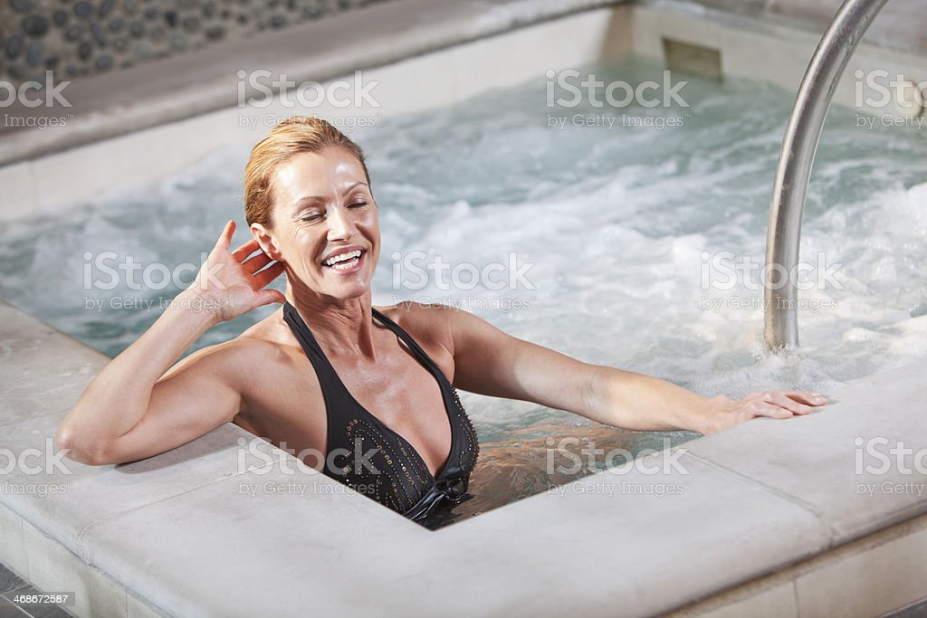 Mature woman in jacuzzi stock photo