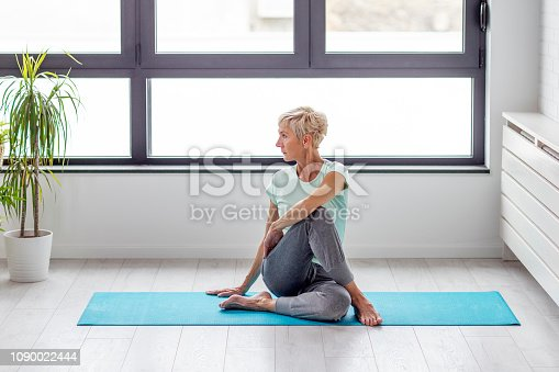 istock Mature woman in joga pose exercise in appartment at rug with window on background 1090022444