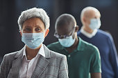 Portrait of mature woman in protective mask looking at camera while standing in a queue