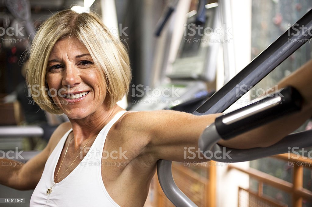 Mature woman in physical therapy office by exercise machines. stock photo