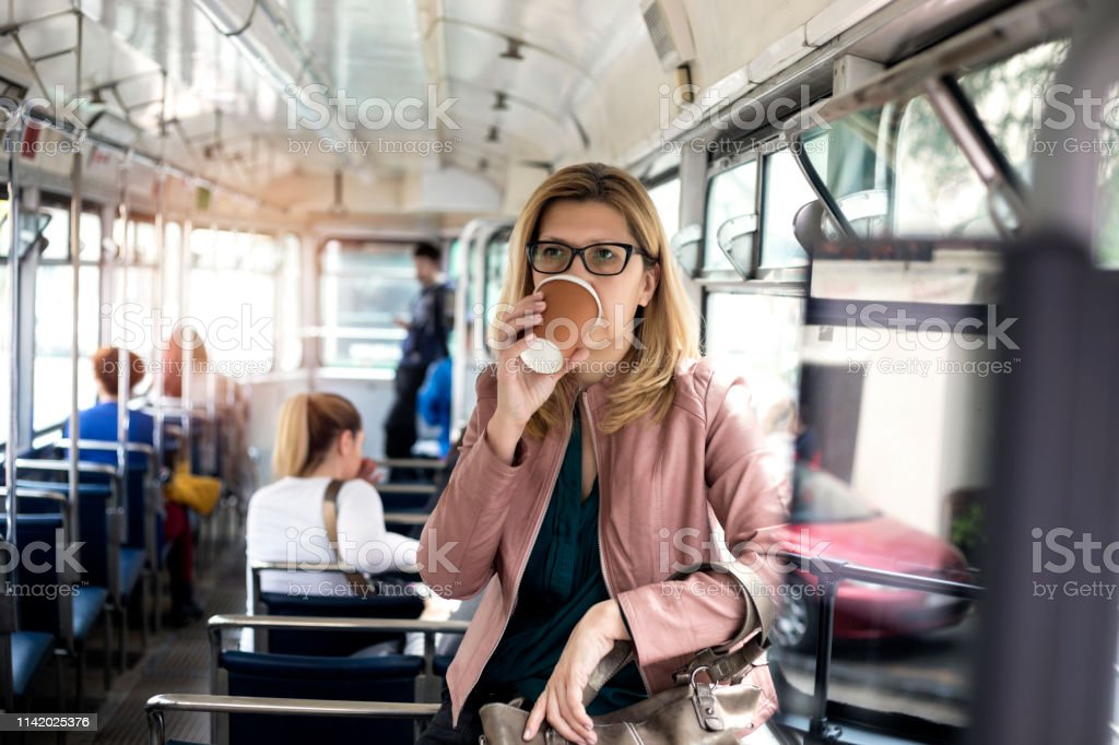 Mature woman riding in public transportation and drinking coffee
