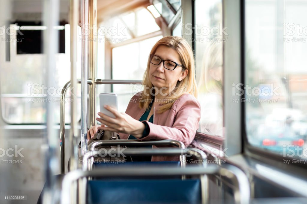 Mature woman riding in public transportation and using mobile phone