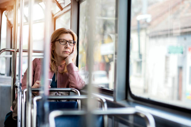 mature woman in public transportation - riding stock photos and pictures