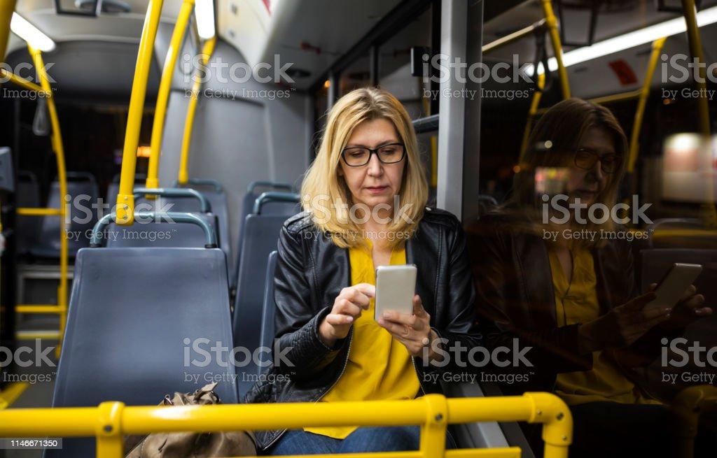 Mature woman riding in public transportation at night