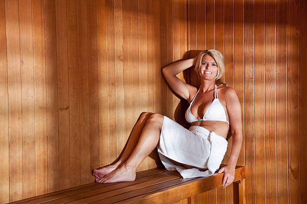mature woman in sauna - older women bikini stock pictures, royalty-free photos & images