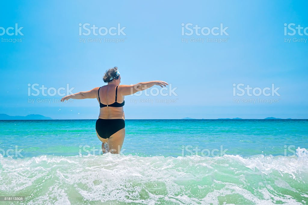 mature woman in swimwear at the sea. stock photo