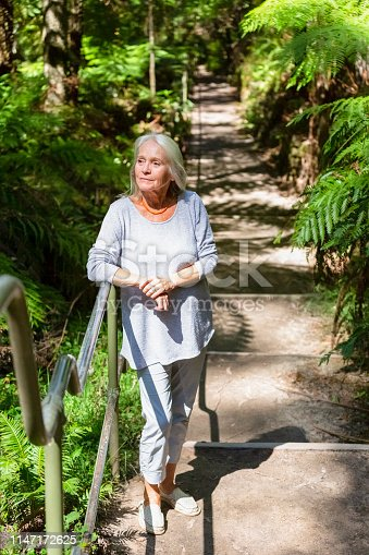Senior woman in the park, background with copy space, full frame vertical, composition
