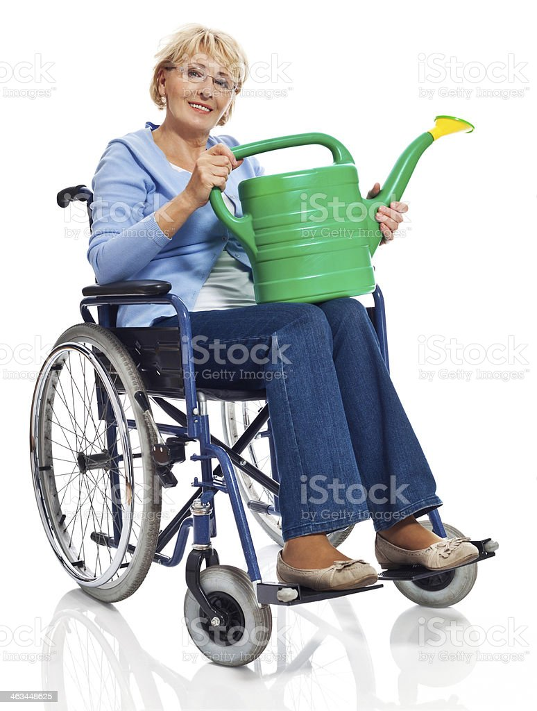 Mature woman in wheelchair Portrait of mature woman sitting in wheelchair with a watering can in hands and smiling at camera. Studio shot on white background. 60-69 Years Stock Photo