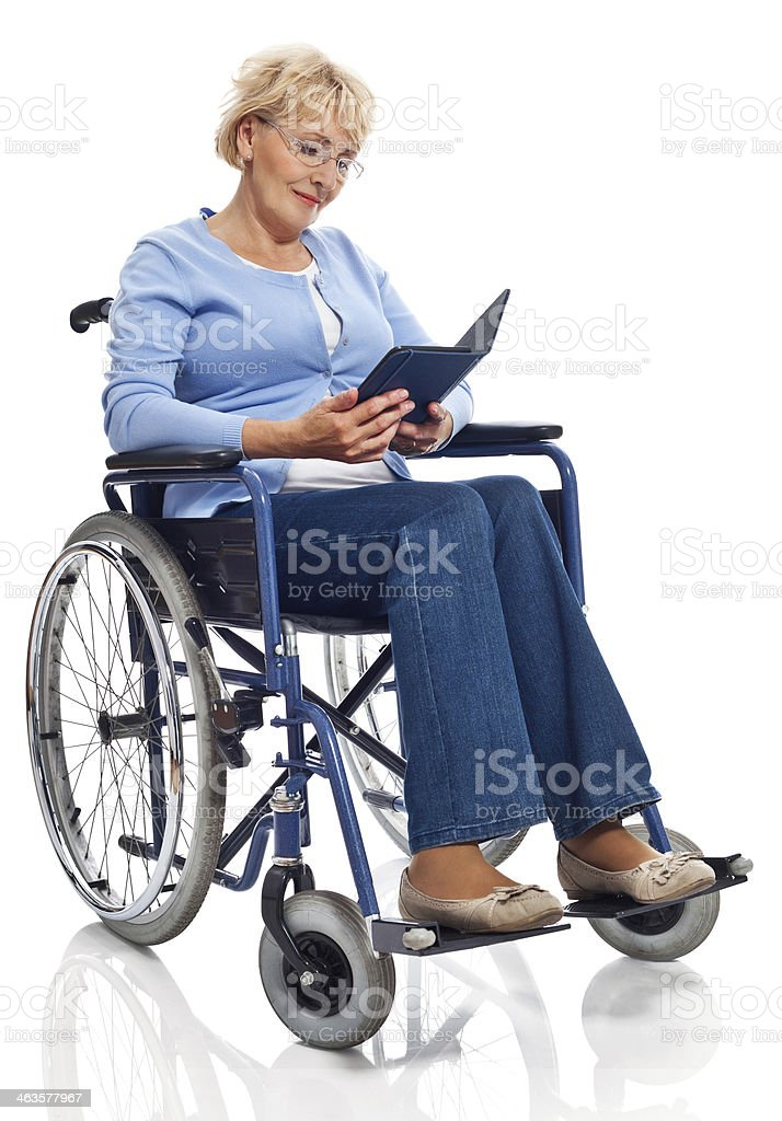 Mature woman in wheelchair Portrait of mature woman sitting in wheelchair and reading an e-bookt. Studio shot on white background. 60-69 Years Stock Photo