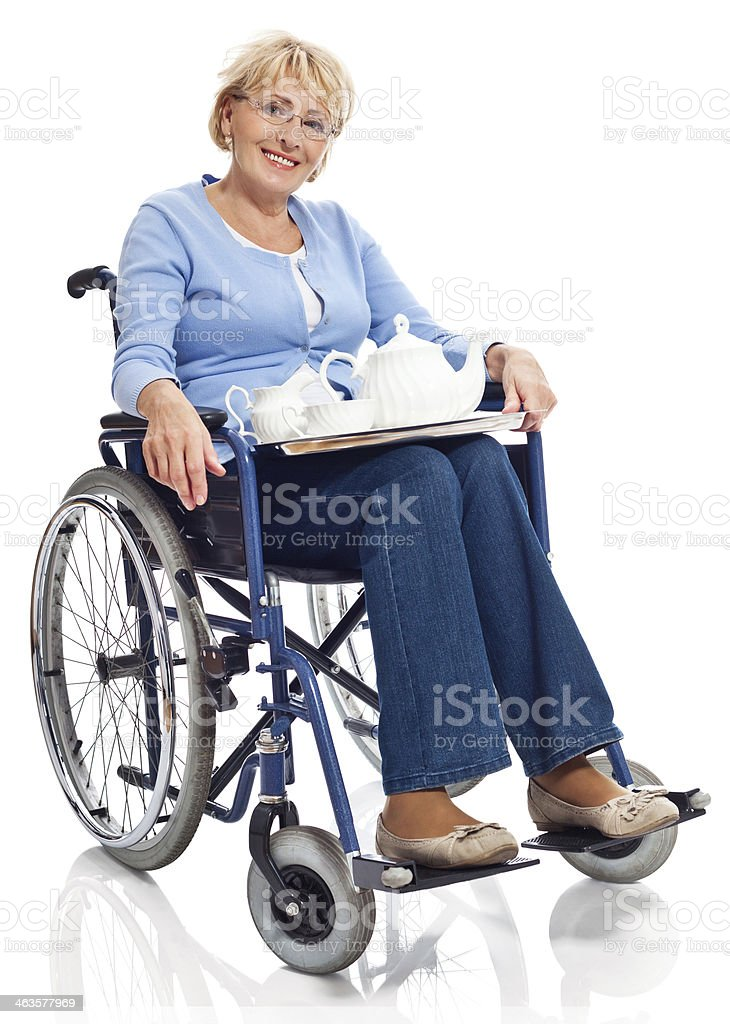 Mature woman in wheelchair Portrait of mature woman sitting in wheelchair with tray with coffee service on her knees and smiling at camera. Studio shot on white background. 60-69 Years Stock Photo