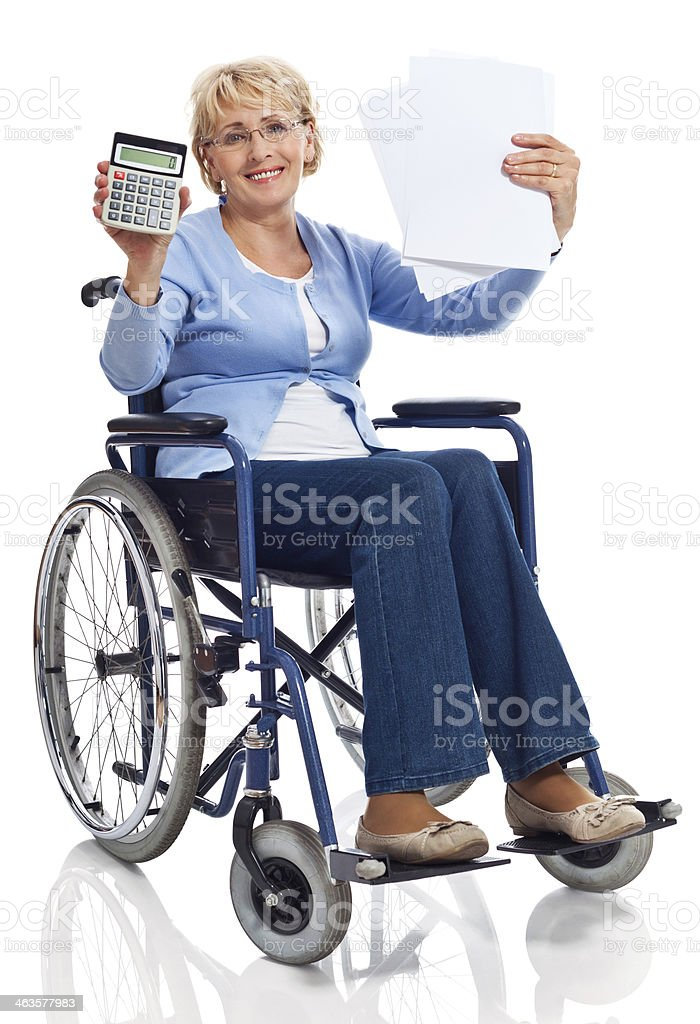 Mature woman in wheelchair Portrait of mature woman sitting in wheelchair, holding a calculator and bills in hands and smiling at camera. Studio shot on white background. 60-69 Years Stock Photo