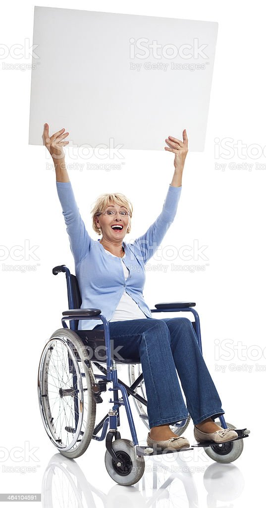 Mature woman in wheelchair Portrait of happy mature woman sitting in wheelchair and holding whiteboard above her head, laughing at camera. Studio shot on white background. 60-69 Years Stock Photo