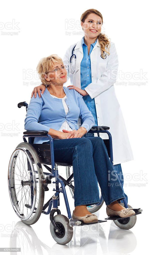Mature woman in wheelchair Portrait of mature woman sitting in wheelchair with a young doctor standing next to her. Studio shot on white background. 60-69 Years Stock Photo