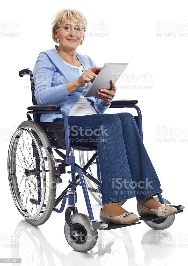Mature woman in wheelchair with digital tablet Portrait of mature woman sitting in wheelchair and using a digital tablet. Studio shot on white background. 60-69 Years Stock Photo