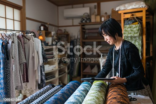 Mature woman inspecting the finished textile fabric she designed after she had it manufactured