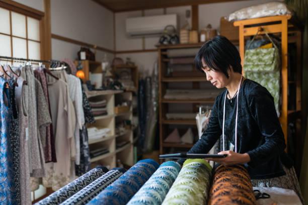彼女は製造後に設計された繊維を終えた生地を検査熟女 - sustainability ストックフォトと画像