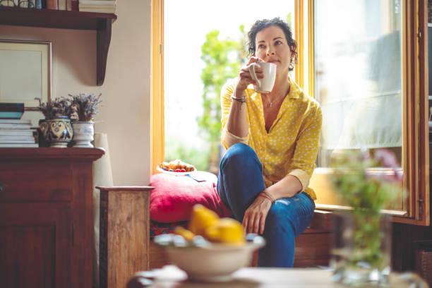 mujer madura es tener el café de la mañana en casa - gente tranquila fotografías e imágenes de stock