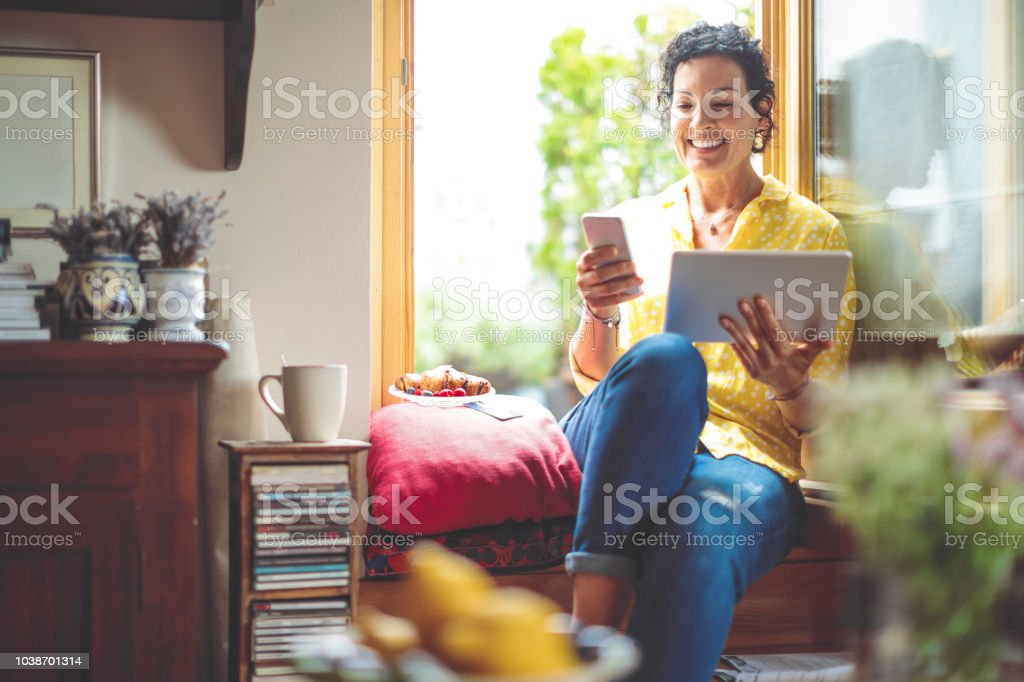 Mature woman is purchasing online at home stock photo