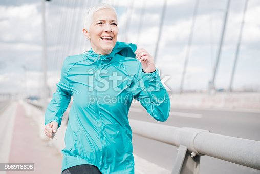 1057638814 istock photo Mature woman jogging and smiling 958918608