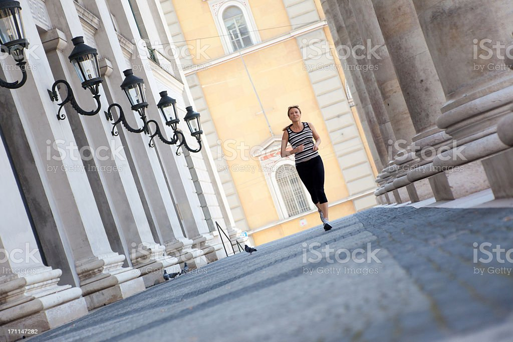 mature woman jogging in the city royalty-free stock photo