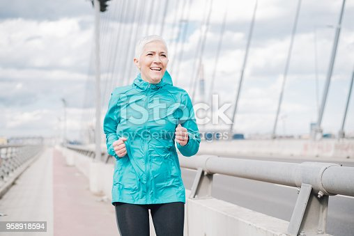istock Mature woman jogging 958918594