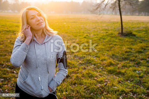 851958232istockphoto Mature woman jogging with Music as motivation for runnng 629255022