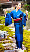 Mature woman joyfully poses at temple in kimono, with both arms up doing double peace signs and a big smile. Ful length image.