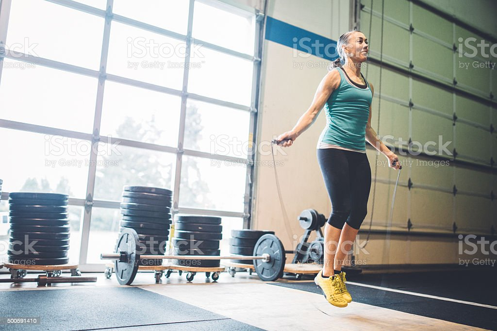 Mature Woman Jumping Rope in Gym Setting stock photo