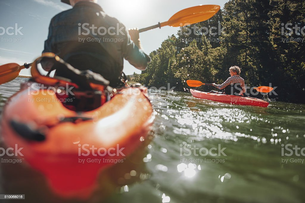 Mature woman kayaking in lake on a sunny day stock photo