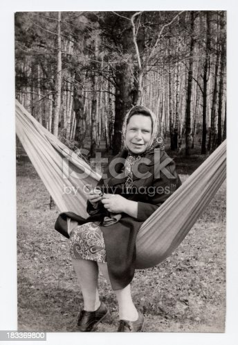 Old photo of a mature woman knitting outdoors