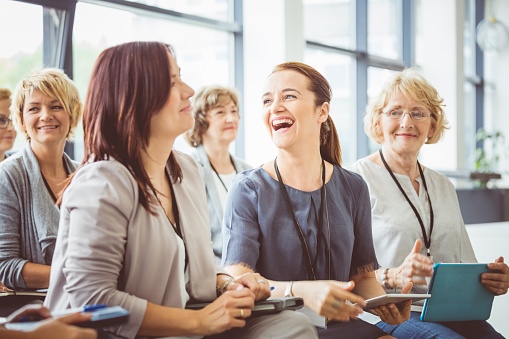 Mature Woman Laughing During Seminar Stock Photo - Download Image Now