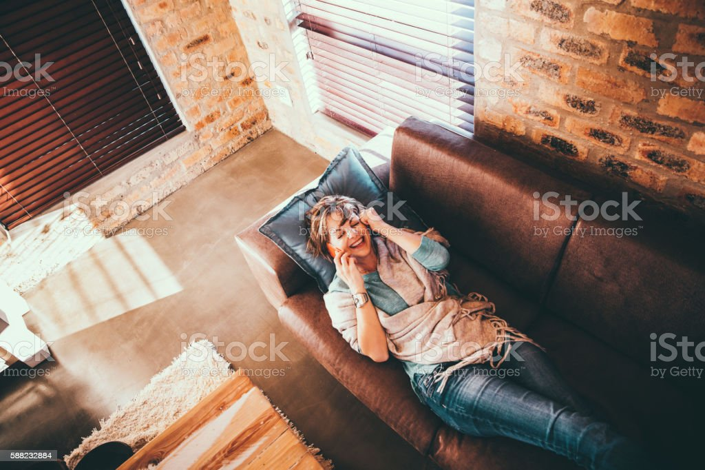 Mature Woman laying on a couch hearing good news over stock photo