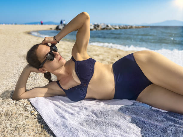 Mature woman laying on the beach wearing sunglasses and a high waist retro swimsuit. stock photo